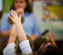 school children with hands in air