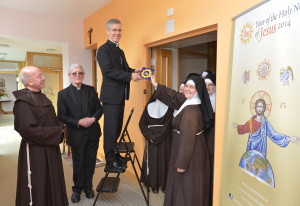 Sr Colette, Abbess of the Poor Clare community in Galway, hands one of the new range of Holy Name tiles to Papal Nuncio, Archbishop Charles Brown watched by Fr Fearghus OFM, Bishop Martin Drennan of Galway and the Poor Clare Sisters.