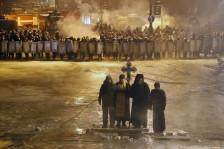 Orthodox priests pray as they stand between pro-EU protesters and police lines in central Kyiv, Jan. 24, 2014.