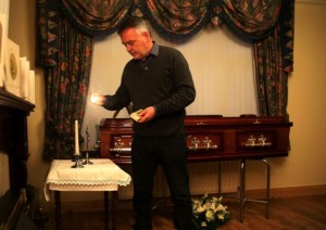 Kieran Megraw lights a candle beside the coffin bearing the remains of his brother Brendan Megraw who was abducted in 1978. Pic courtesy: www.newsletter.co.uk