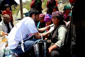 A doctor from MSF tends some wounded Nepalese.