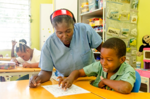 Teacher Delicarme Chery assists 12 year old Fabenson during art class. Photo: NPH Haiti.