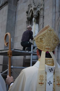 Archbishop Eamon Martin, wearing the pallium, watches on as the statue of St Patrick on the front of St Patrick's Cathedral in Armagh is refitted with a crozier.