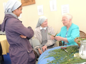 Juli Thottungal and Lucyna Wisniowska, Sisters of St Peter Claver, and Kay Mulhall, Brigidine's, weaving St Brigid's cross