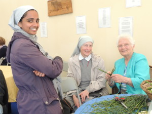 Juli Thottungal and Lucyna Wisniowska, Sisters of St Peter Claver, and Kay Mulhall of the Brigidines who is weaving a St Brigid's cross.