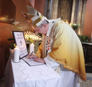 Archbishop Diarmuid Martin of Dublin signing the book of condolence in St Mary's Pro Cathedral after a mass to remember the victims of the Paris tragedies. Pic John Mc Elroy.