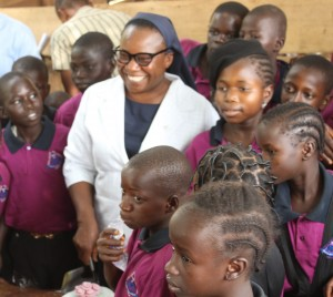 Sr Anne Falola, OLA with children of Durumi IDP Camp in Abuja cutting a cake with marked the opening of the Maria Centre.