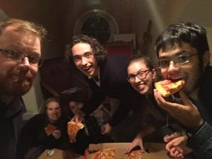 youth workers and Fr Alan celebrate arrival in Cork with pizza